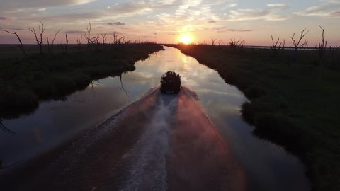 An airboat powers down a waterway during a beautiful southern Louisiana sunset over a bayou and stretch of water dotted with silhouettes of dead trees.