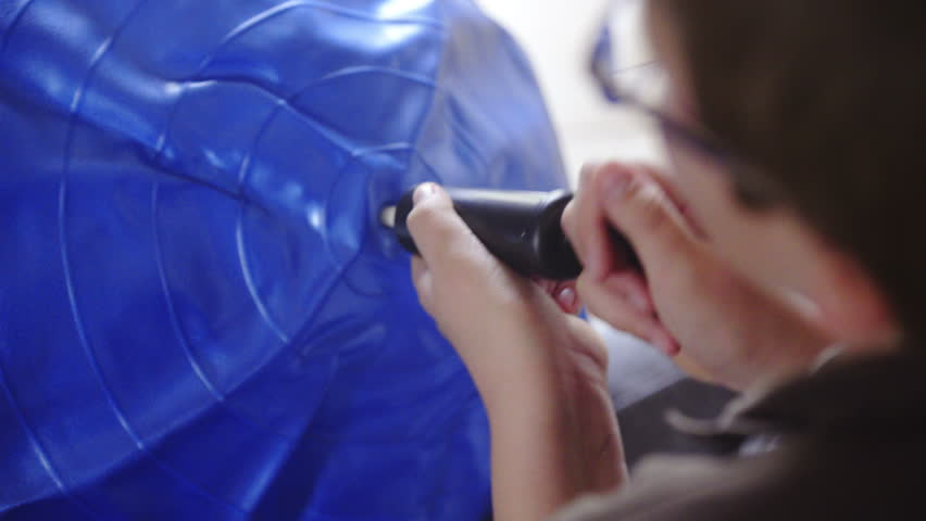 Over shoulder view of inflating blue ball 4K. Boy with glasses pumping big gymnastic ball at home. | Shutterstock HD Video #12656948