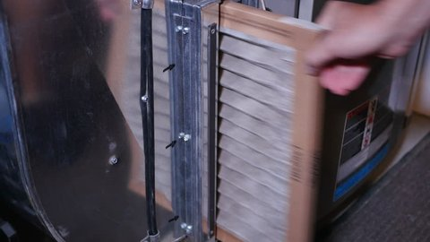 Replacing a dirty air filter in a household furnace unit.