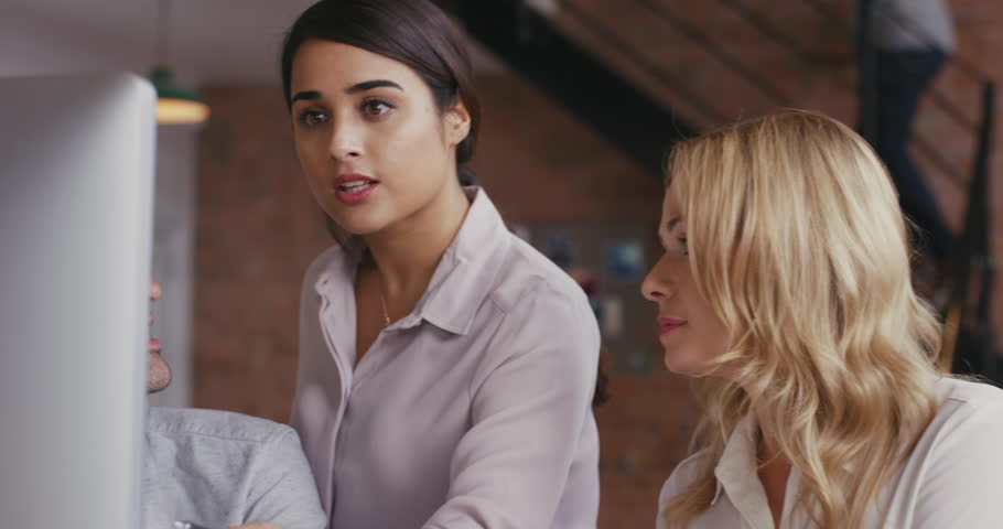 Woman team leader meeting with diverse group of startup business people pointing at computer screen in trendy modern office with red brick walls slow motion | Shutterstock HD Video #12702446
