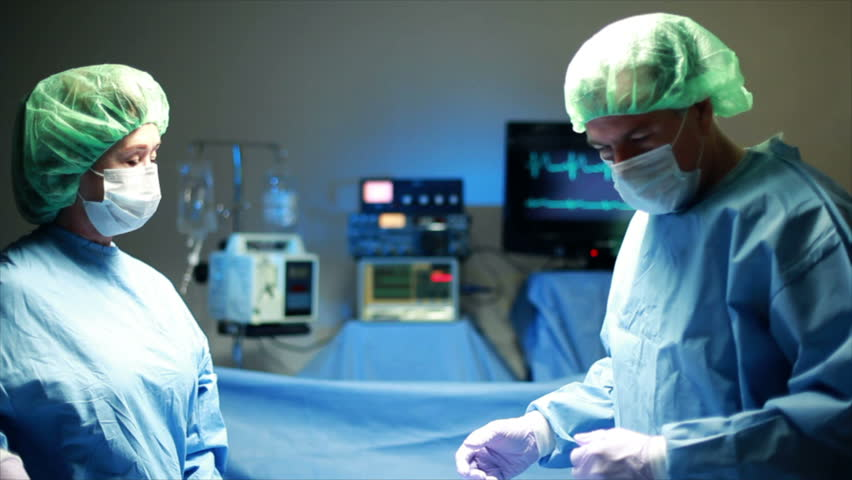 Two surgeons performing surgery are assisted by a surgical nurse.