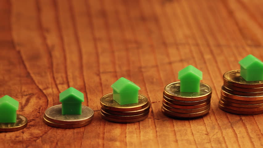 House mortgage concept with small plastic house models on top of stacked coins