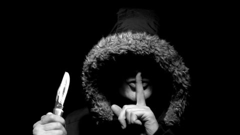Ominous Maniac in a hood speaks shhh and threatens with a knife at night