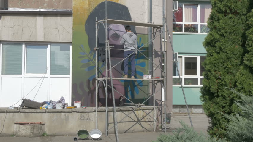 Talented Young Graffiti Artist Standing On Scaffold And Painting Mural With  Brush. Performance,raw Part 93