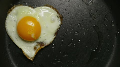 Couple eggs in frying pan. Form of heart. Cooking fried eggs in the form of heart. ?lose-up 4K UHD.