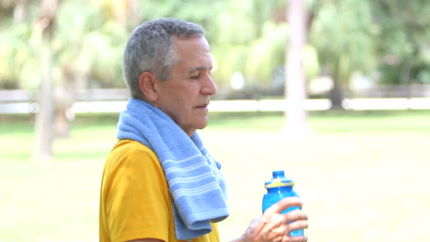 Senior fit healthy man 'toasting' the camera with a sports water bottle.
