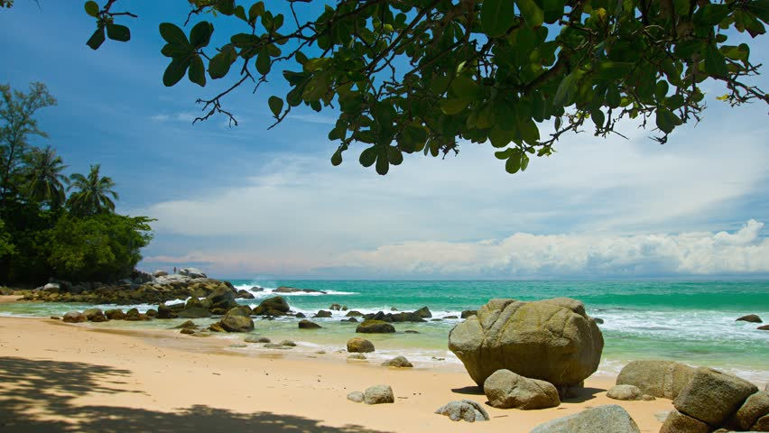 Gentle waves wash over a rocky. boulder strewn. sandy. tropical beach with dense. threatening clouds building on the distant horizon. Video 4k