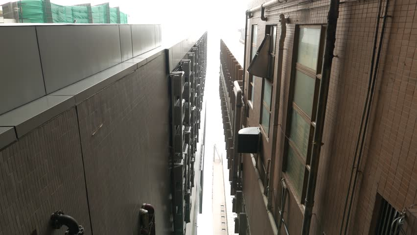 Narrow gap between high towers, look upwards while move along byside passage, backstreet within urban block, surrounded by Russell and Tang Lung Streets, Wan Chai district of Hong Kong Island.