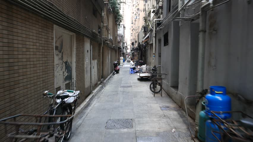 HONG KONG - MARCH 31, 2015: Narrow back side passage between towers at urban Causeway Bay area, people group sit around play card game at break time. Wan Chai district of Hong Kong Island, daytime.