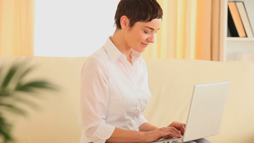 smiling woman using a laptop in her living room hd stock footage clip - Losing Job Getting Fired From Job