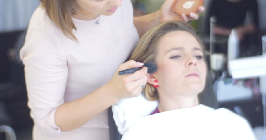 Woman, Female Stylist, Beautician is Putting a Powder with Brush to the Model's Face, Anxious or Concentrated Face, Making a Makeup for a Woman, Model with New Hairstyle, Curls, Woman is sitting in | Shutterstock HD Video #12917747