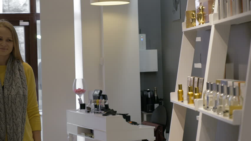 Man and woman are standing by the shelf in perfumery shop. They are trying fragrance with paper tester. | Shutterstock HD Video #12967286