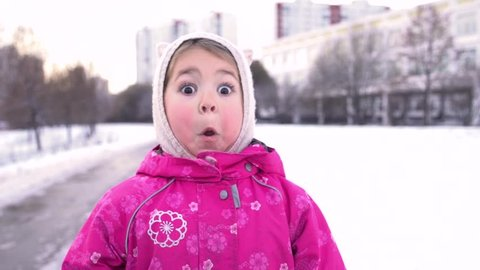 Close-up of 4 Year Old Little Funny Girl Acts Very Surprised on winter street. Slow motion.