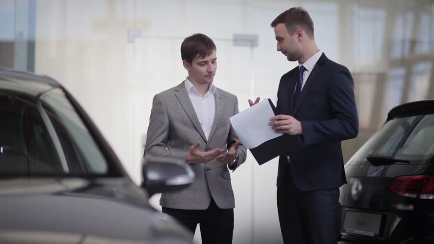 Couple With Car Dealer Signing Purchase Contract On Tablet Stock