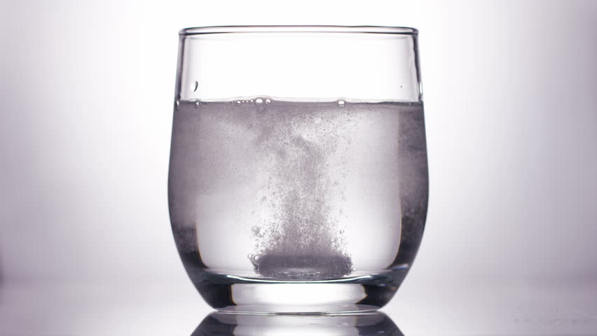 4K Effervescent tablet dropped into a glass of water, in slow motion
