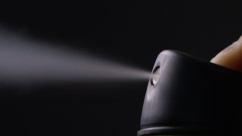 Aerosol can being sprayed against a black background, in slow motion at 240fps