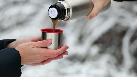 Woman holding cup from thermos in hands at snowy branches of winter trees background. Man pouring hot coffee with milk in cup from thermos.