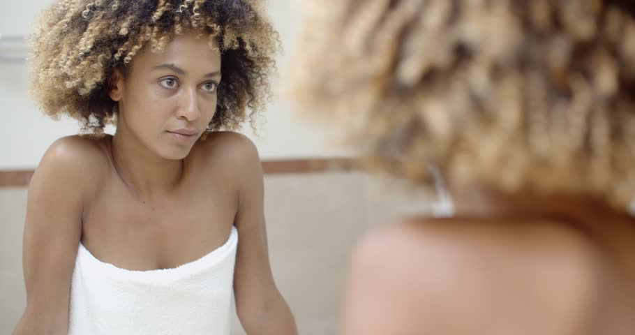 Young black woman checking her face in the mirror in bathroom