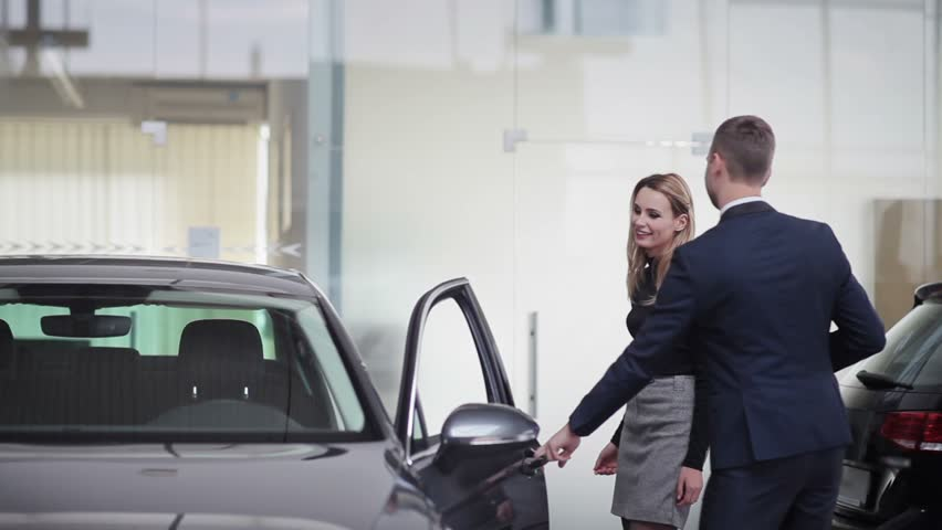 Handsome young car salesman assisting a client in the dealership