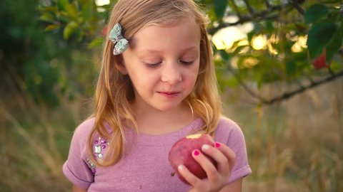 A cute little girl takes a bite out of a fresh apple from a tree and makes a face, and then smiles