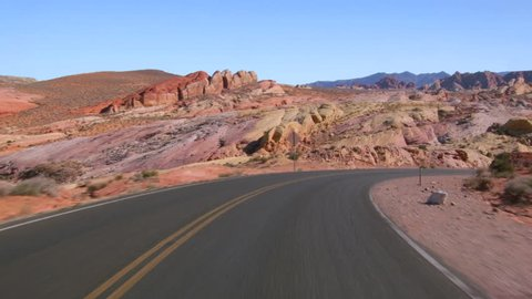Driving USA: Scenic point of view car shot showing empty desert road and pink and yellow sandstone in Valley of Fire State Park, Nevada