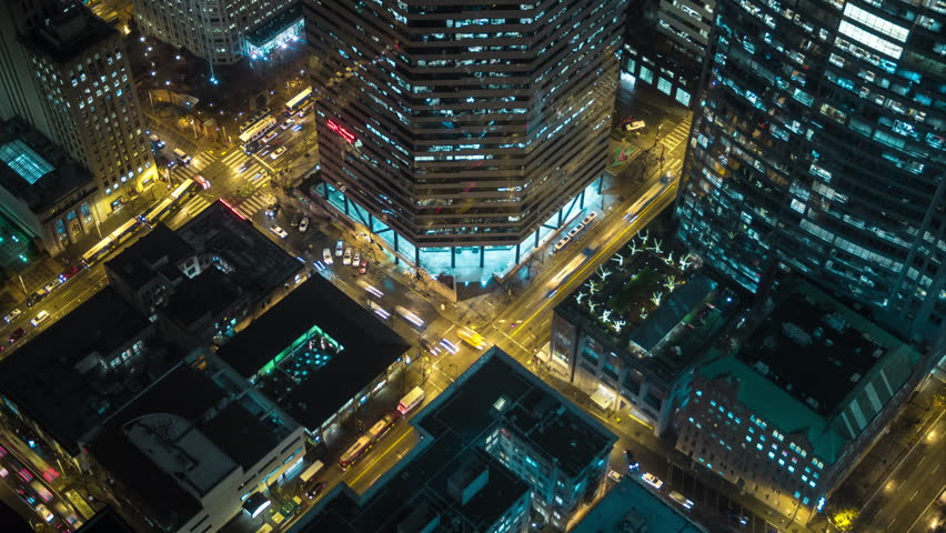 Aerial Bird's Eye view of Downtown City Streets at Night in Business District Cityscape Time-lapse