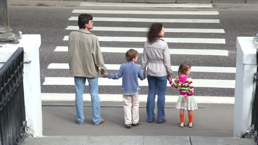 Family goes by pedestrian crossing road, parents keep childrens hands, car ride by road in front of them and behind when they passed
