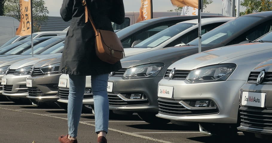 STRASBOURG, FRANCE - CIRCA 2015: Woman walking between rows of Volkswagen cars and choosing the right Volkswagen after the Volkswagen Gate - Volkswagen emission scandal