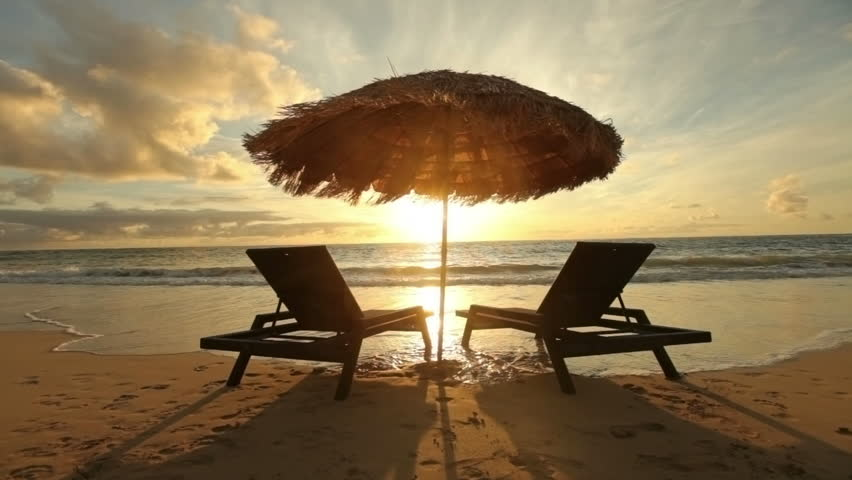 Cinemagraph - Sunrise at tropical beach with chairs and hut. Looping Motion Photo.