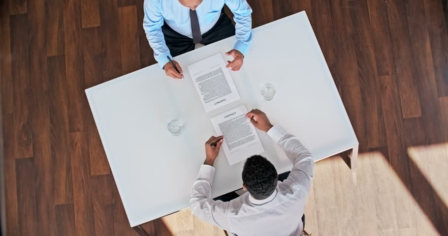 Two business representatives signing contract and then shaking hands | Shutterstock HD Video #13102946