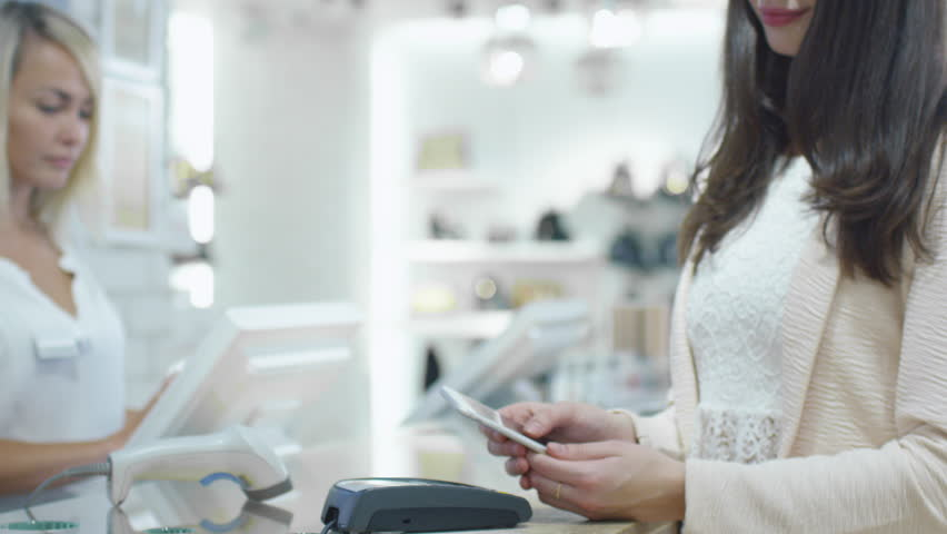 Young woman is paying with her smartphone application at the cash desk in a department store. Shot on RED Cinema Camera in 4K (UHD). | Shutterstock HD Video #13107986