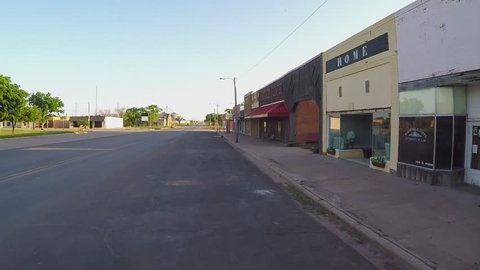 CROWELL, TX/USA - August 3, 2015: POV driving by storefronts in a farm town square. A driver passes by several small businesses in a small rural city along a vacant road in downtown area.