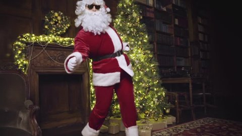 Santa Claus in sunglasses dancing and looking at the camera, christmas tree with lights, decorated fireplace in background, tracking shot