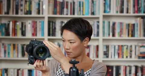 Attractive asian woman setting up digital camera on tripod at home using creativity and inspiration in front of colorful bookshelf