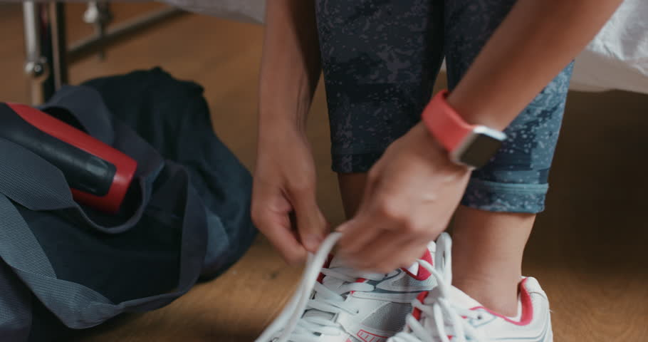 Healthy woman at home getting ready for gym workout tying shoe laces with smart watch checking fitness data