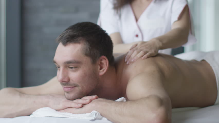 Handsome man is getting a relaxing massage from a woman masseur in wellness center. Shot on RED Cinema Camera in 4K (UHD). | Shutterstock HD Video #13175876