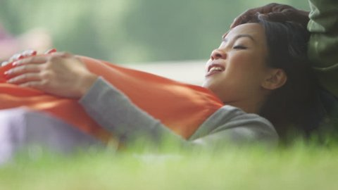 4K Happy pregnant couple relaxing in the park, feeling baby kicking. Shot on RED Epic.