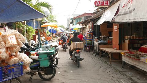 JAKARTA, INDONESIA - MARCH 10, 2015: Walk on sunny narrow market street, unidentified people, bajaj, motorbike, stalls, wheel carts, mobile kitchen. Chinatown like area