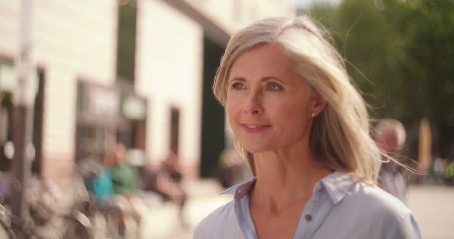 Smiling mature woman with grey hair walking confidently down a city street while holding shopping bags | Shutterstock HD Video #13192043