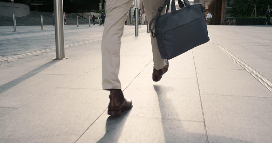 Close crop of businessman feet walking in city. Man commuting to work. Steadicam shot in slow motion with warm natural light on sidewalk