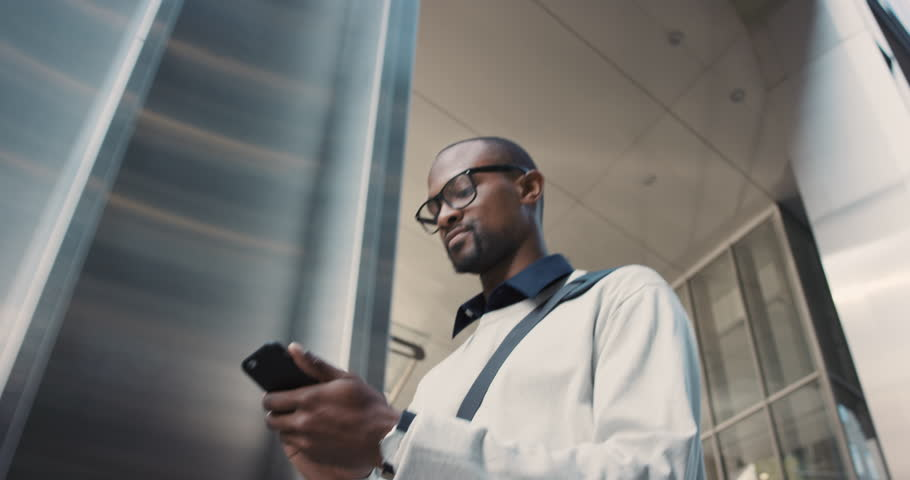 African American Man using business app on smart phone walking in city. Handsome young businessman communicating on smartphone smiling confident. Urban black male professional commuting in his 20s | Shutterstock HD Video #13200206