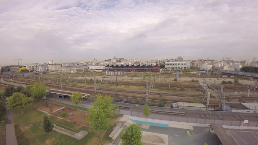 Paris, 18th arrondissement- Aerial view of TGV high speed train passing at Gare du with Halle Pajol and city skyline in background