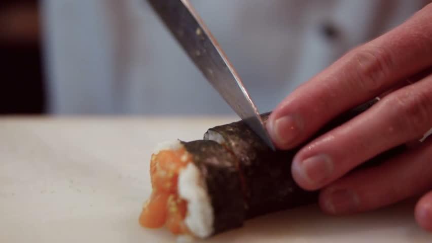 chef in restaurant preparing and Cutting sushi rolls healthy food