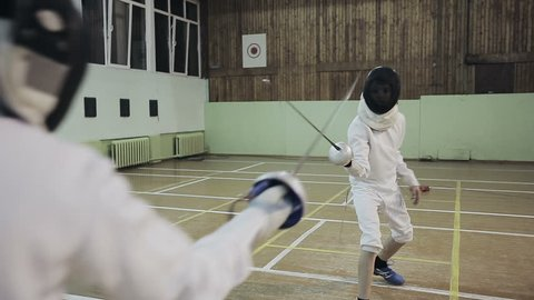 Young guys fencers practicing fencing duel