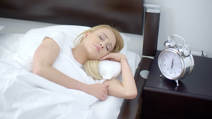 Close Up Pretty Woman Sleeping On Her Bed With Old Fashioned Alarm Clock On  The