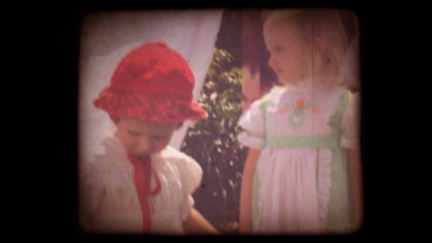 Old home movie of kids playing in their back yard with a vintage 8mm film look. Shots are recent, but very authentic looking. Includes projector audio.