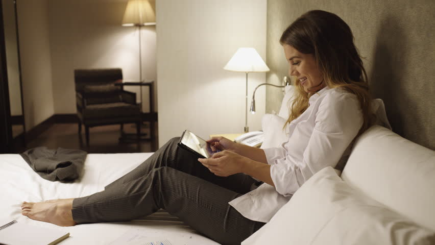 Young Business Woman Sitting On Bed In A Hotel Bedroom Chatting