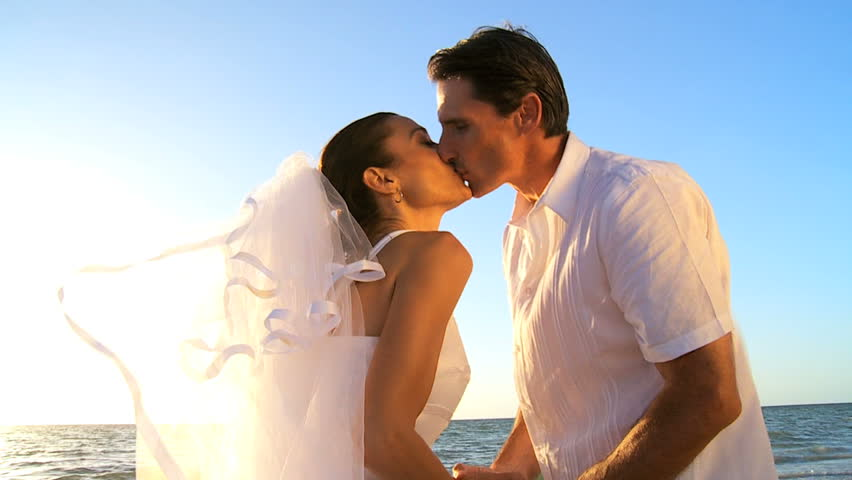 Bride & groom sharing a kiss after their wedding ceremony on the beach filmed at 60FPS