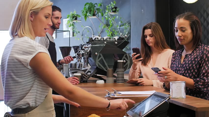 Customer makes mobile online cashless payment with cell phone, waitress behind the counter confirms payment on touch screen device in modern trendy coffee shop cafe | Shutterstock HD Video #13307609