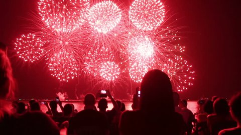 spectators with smartphones watching fireworks
